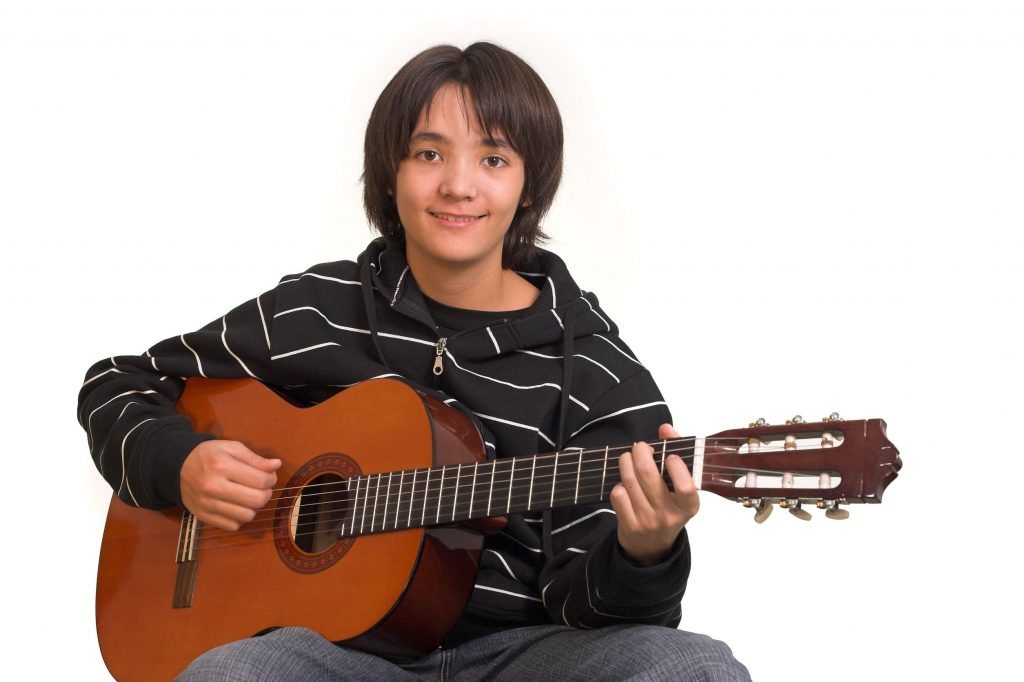 2005404 - smiling boy playing guitar on white background