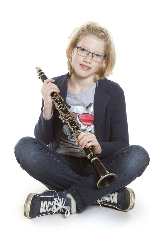 35305242 - young blond girl sits holding clarinet in studio against white background